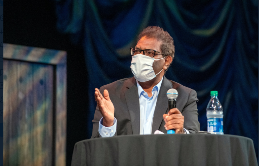Dr Edwin Michael, an epidemiologist with USF, holds a mic and wears a mask at an event in Oct