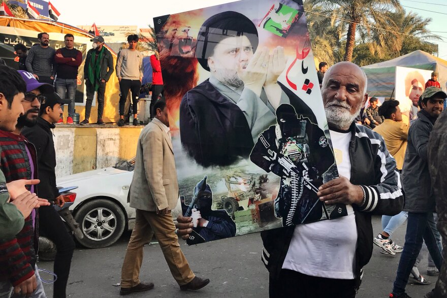 A Sadr follower in Tahrir Square holds a photo of the Shiite cleric along with some of his fighters. Sadr has called on followers not to carry his photo, but many do.