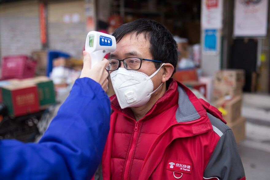 A courier gets his temperature checked. In Wuhan, individuals are required to get it checked twice a day.