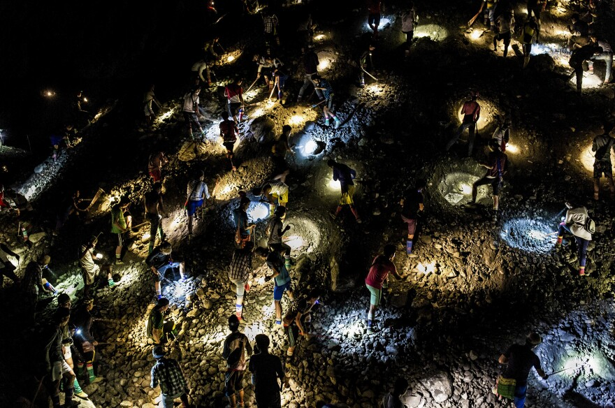 Freelance miners use flashlights to search for jade at night, during company off-hours, in Hpakant in 2019.