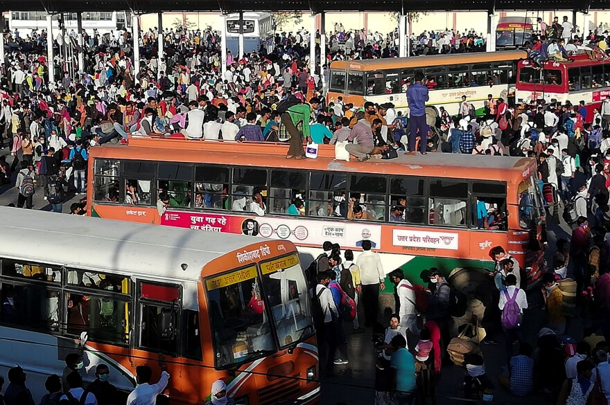 Migrant workers and their families gather outside a New Delhi bus terminal.