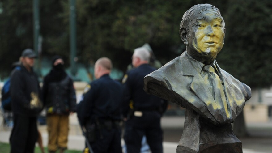 A defaced bust of former city councilmember Frank Ogawa sits outside Oakland, Calif., City Hall on Sunday.