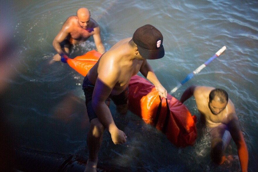 Rescuers remove the body of a migrant after their boat sank off the coast of in Zuwara, Libya, on Thursday.