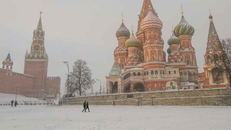 People walk under a heavy snowfall in front of St. Basil's Cathedral and the Kremlin in Moscow in January.
