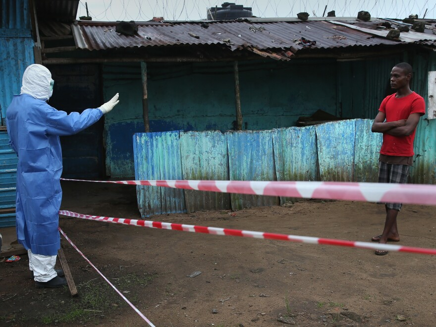 A doctor keeps a pedestrian away from the JFK Ebola treatment center on October 13, 2014 in Monrovia, Liberia. (Photo by John Moore/Getty Images)