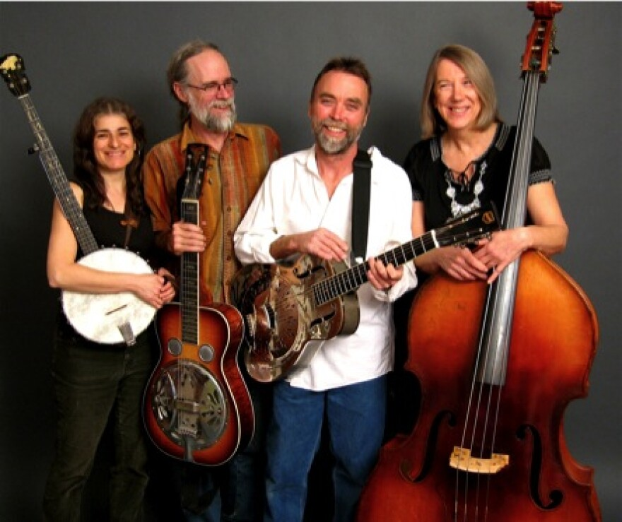 Band members stand holding various stringed instruments from left to right are Gloria Attoun, Michael Bauermeister, Paul Ovaitt, Rebecca Mayer.