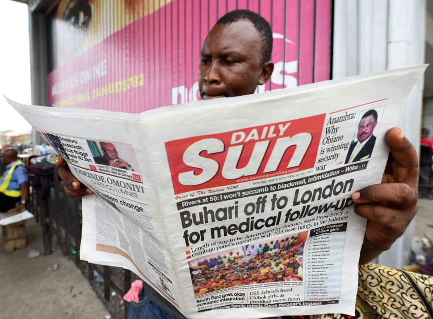 """A Nigerian man in Lagos reads a newspaper addressing President Mohammadu Buhari's """"follow-up medical consultation"""" in London."""
