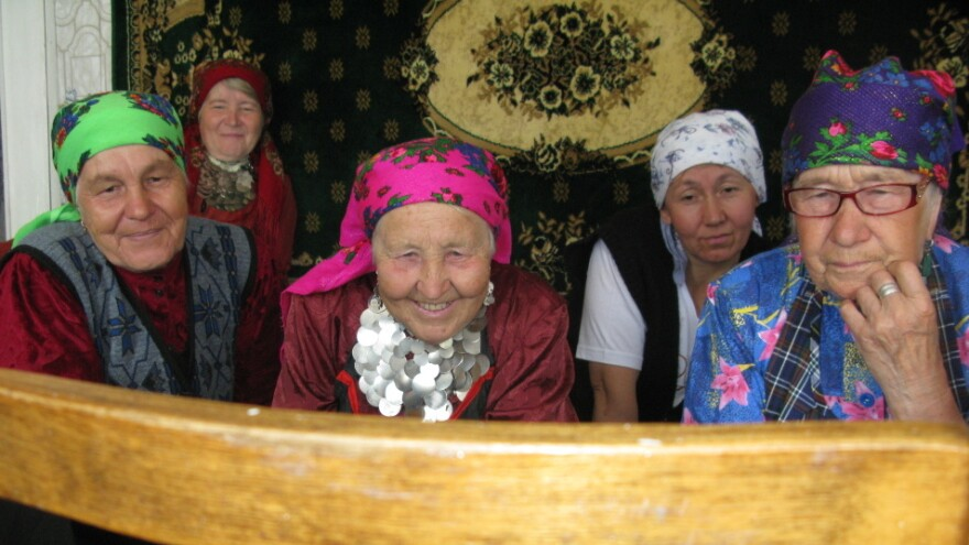 """The """"Buranovo Babushkas"""" watch video, for the first time, of two of their members appearing on Russia's <em>Who Wants to Be a Millionaire?</em> program."""