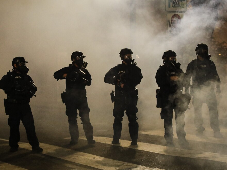 Federal officers are surrounded by smoke as they push back demonstrators during a Black Lives Matter protest at the Mark O. Hatfield United States Courthouse on Wednesday in Portland, Ore.