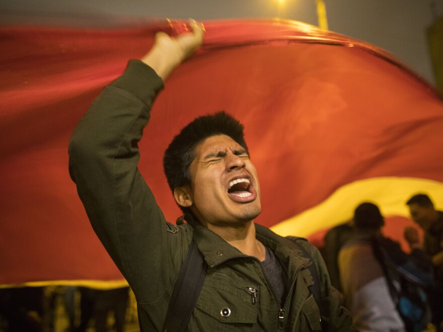 A supporter of Peruvian President Martín Vizcarra chants slogans outside the legislature building in Lima on Monday night, not long after Vizcarra dissolved Congress. Opposition lawmakers defied the president's order and voted to suspend him from office.