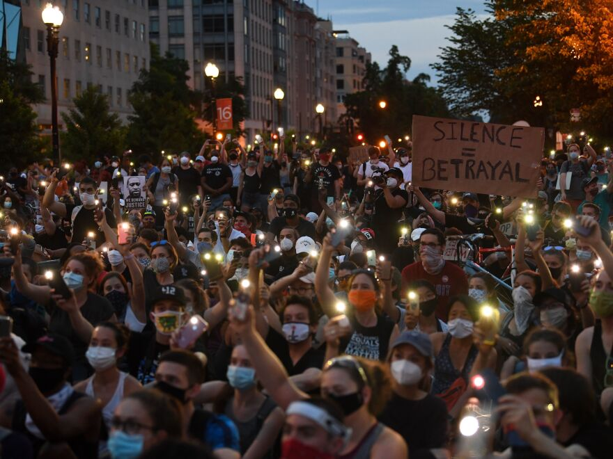 Protesters in Washington, D.C., hold up their phones during a demonstration outside the White House over the death of George Floyd.