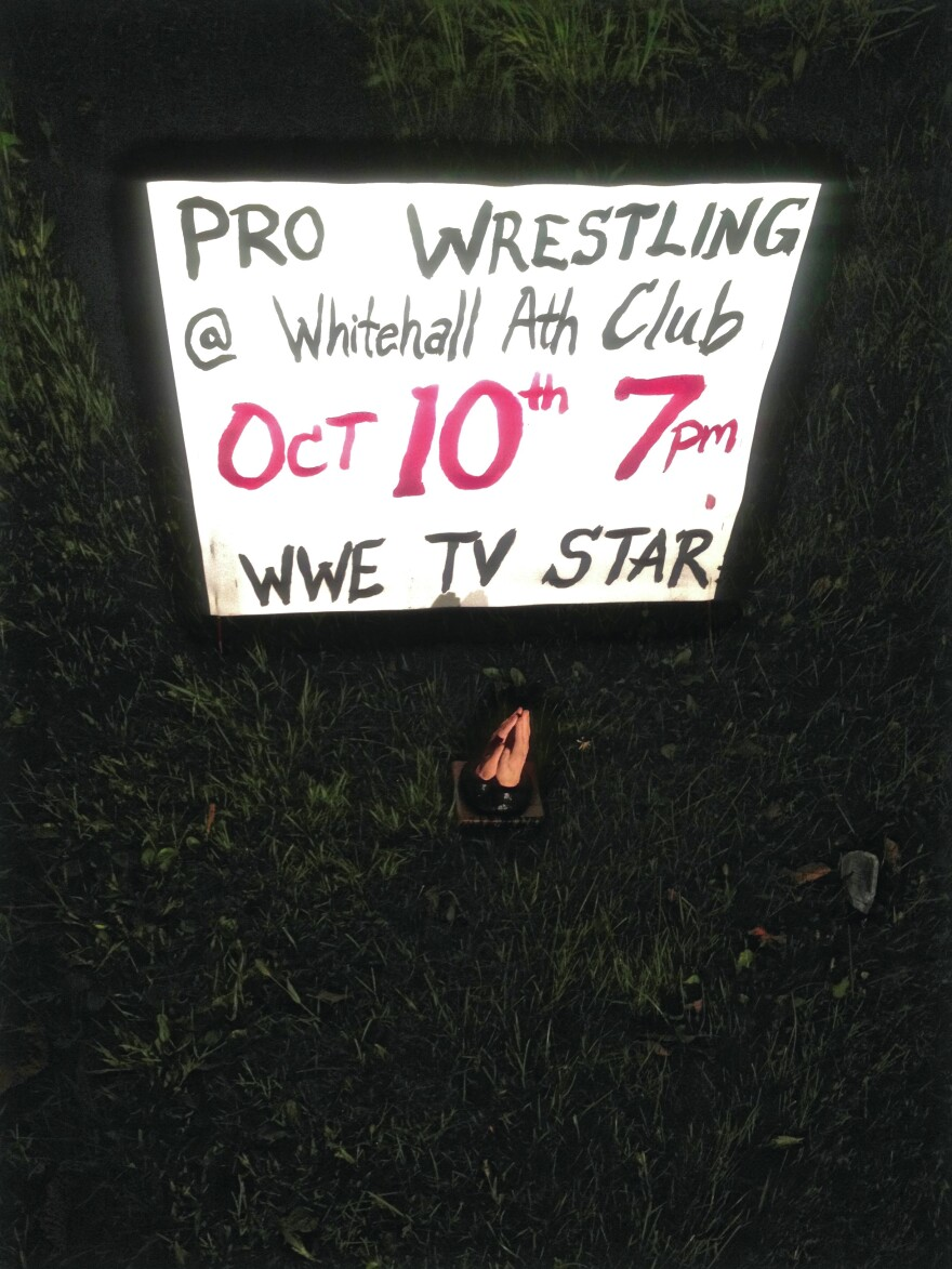 """Sharlet photographed this pair of plastic, painted hands in front of a homemade lawn sign that reads """"PRO WRESTLING."""""""