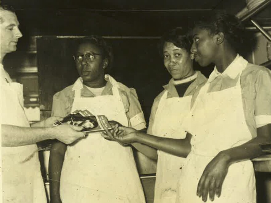 Ollie McClung Sr. hands religious tracts to employees. Most of Ollie's Barbecue's employees were black.