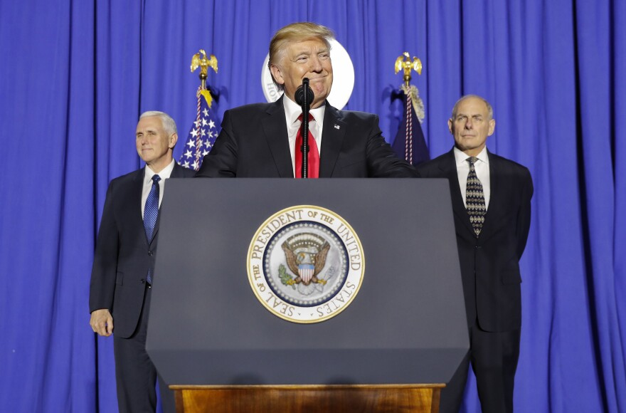 President Trump, accompanied by Vice President Pence (left) and Homeland Security Secretary John F. Kelly, pauses while speaking at the Department of Homeland Security.