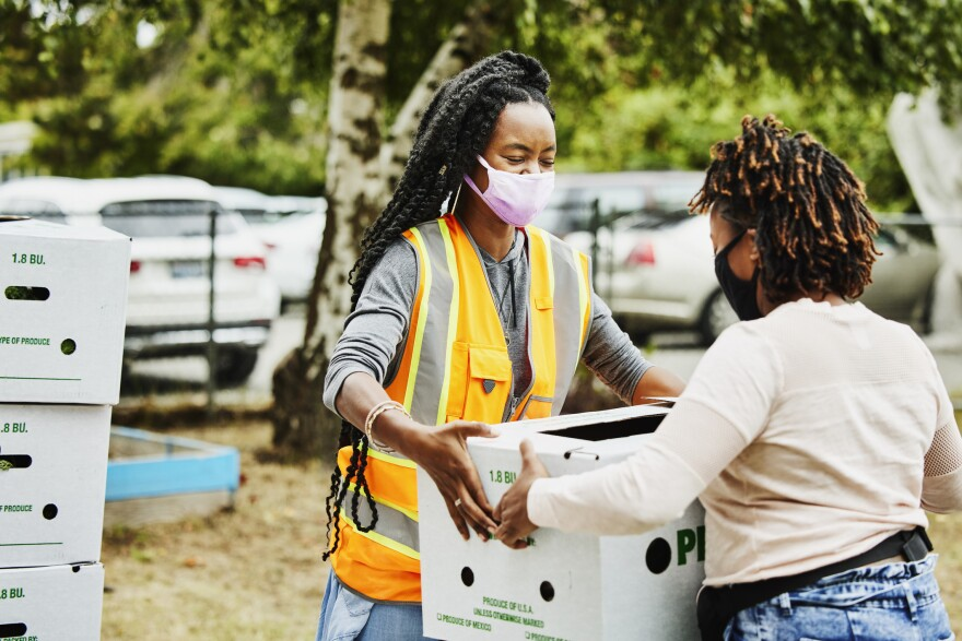 Volunteers wear face masks as they give away boxes of food at a community center. (Getty Images)