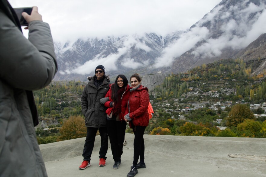 Tourists pose for photos on a medieval fort near the town of Karimabad in the highlands of Pakistan.