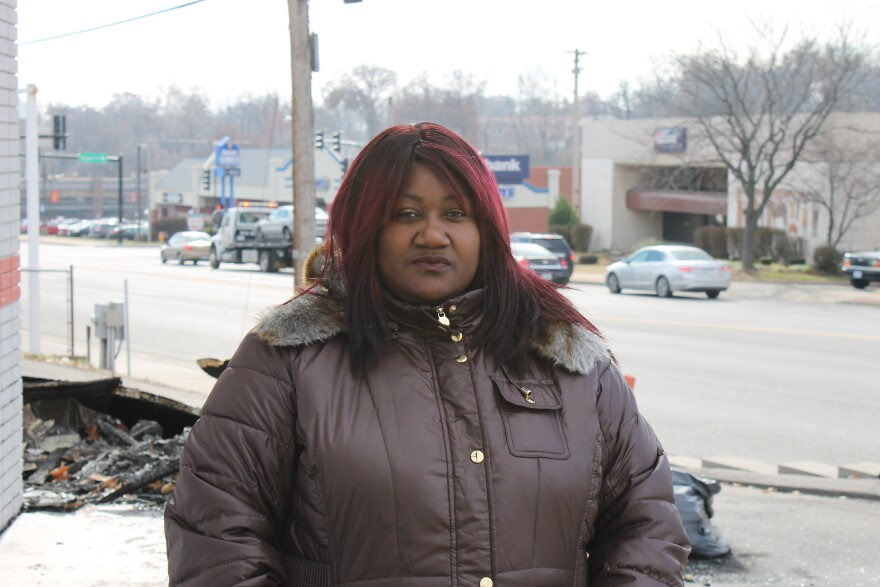 Jeniece Andrews stands in front of the remains of her store on North Florissant Avenue in Ferguson.