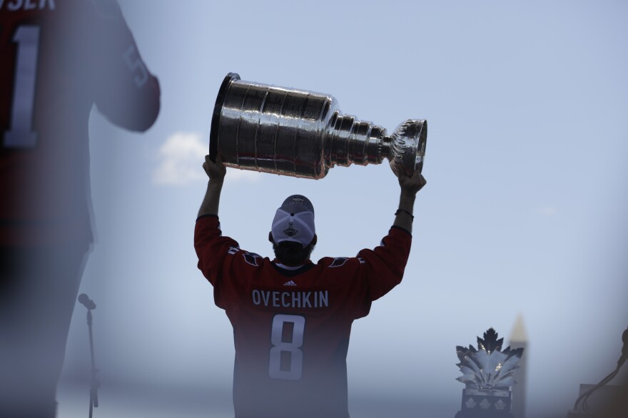 Capitals forward and team captain Alex Ovechkin holds the Stanley Cup above his head during the victory parade.