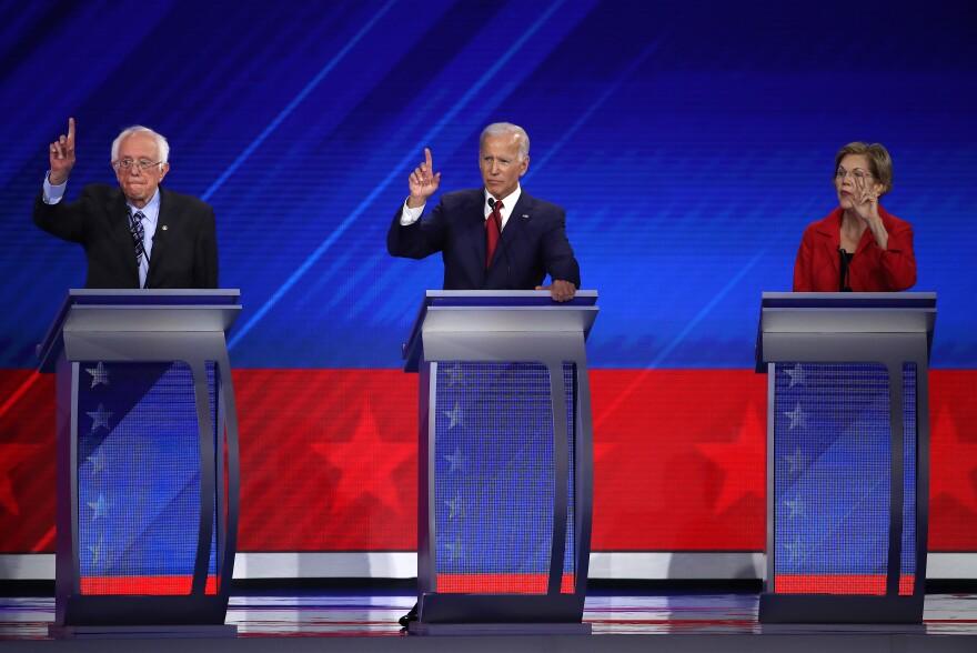 Sanders, Biden and Warren raise their hands during the debate.