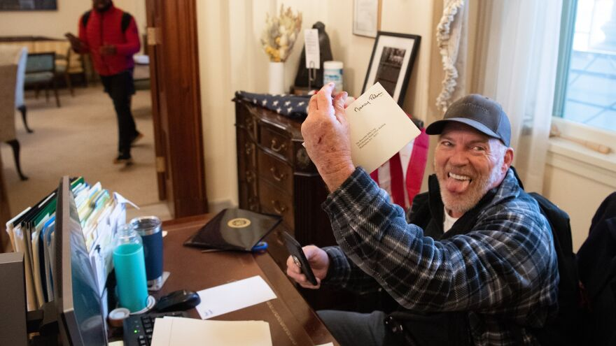 Richard Barnett holds a piece of mail as he sits inside the office of House Speaker Nancy Pelosi after rioters breached the U.S. Capitol. He bragged about leaving a note containing a sexist slur for Pelosi.