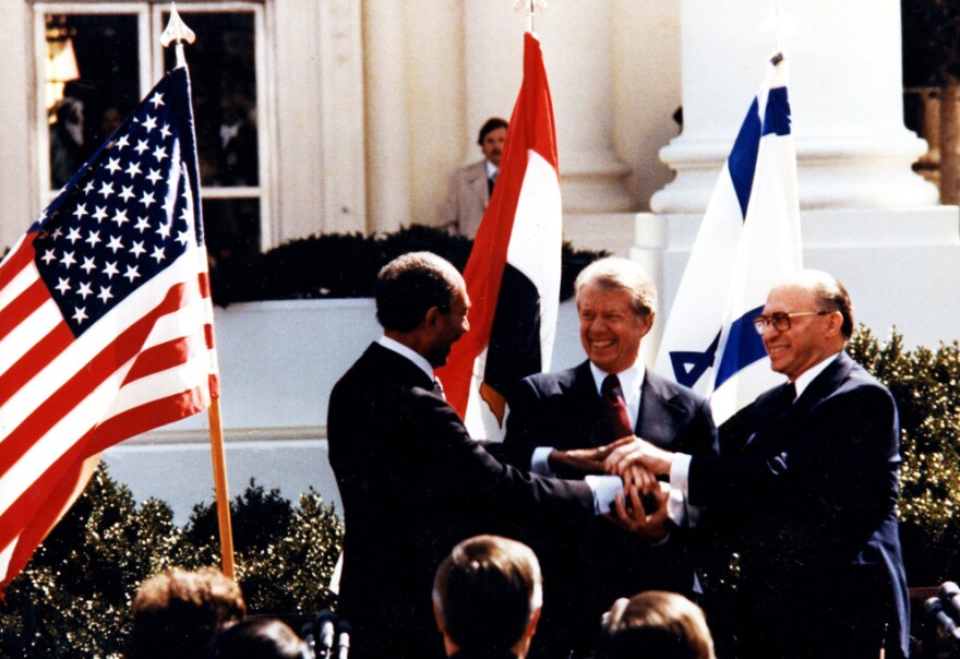 Egyptian President Anwar Sadat (left), U.S. President Jimmy Carter and Israeli Prime Minister Menachem Begin shake hands during the White House signing of the Middle East peace accord in March 1979.