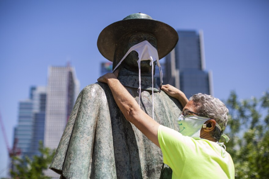 Jeff Levine places a face covering over the Stevie Ray Vaughan statue at Auditorium Shores.