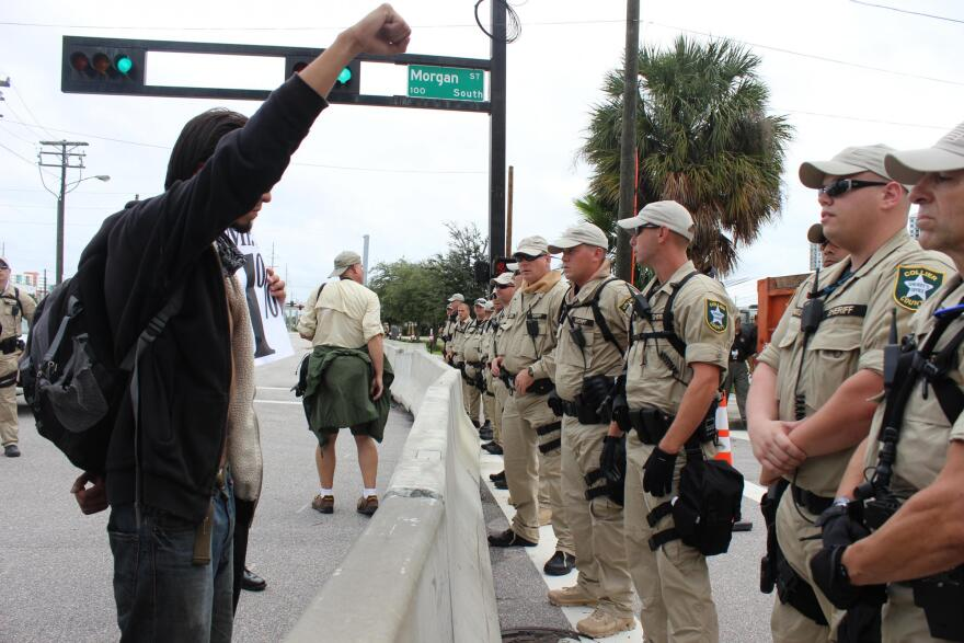 black-clad protestor holds up fist in front of uniformed offcers