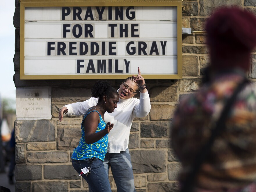 Women dance and pray to music over a loudspeaker outside a church following the funeral for Freddie Gray in 2015.