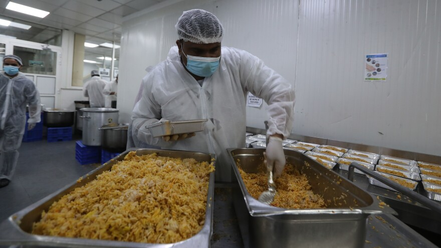 Qatar charity workers prepare food parcels for migrant laborers living under quarantine on April 16 amid the coronavirus pandemic in Doha. A restaurant better known for fine dining has lent its facilities to Qatar Charity to feed migrant workers, of whom tens of thousands are strictly confined to an area of Doha's southern industrial area.