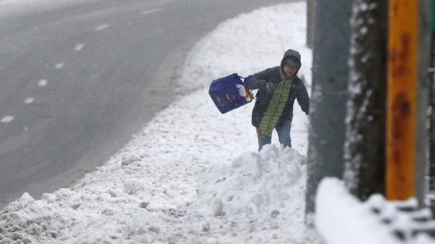 A person stumbles through deep snow Monday in Marlborough, Mass.