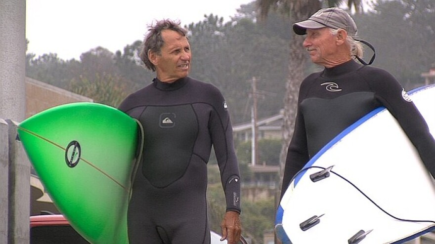 Vietnam veterans James Lischer, left, and Bobby Lux get ready to surf at Del Mar. Since the 1960's, surfing has helped them open up about their experience in Vietnam.