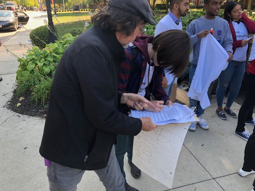 A voter signs a petition for a signature gatherer working in Columbus last year.