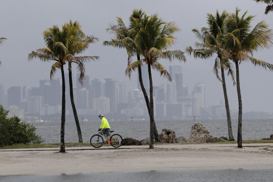 The Miami skyline is shrouded in clouds as a cyclist rides along Biscayne Bay. The National Oceanic and Atmospheric Administration has predicted an unusually active hurricane season this year, with more frequent and intense storms in the Atlantic Ocean. Seas made warmer by climate change are fueling stronger hurricanes, according to the newest research.