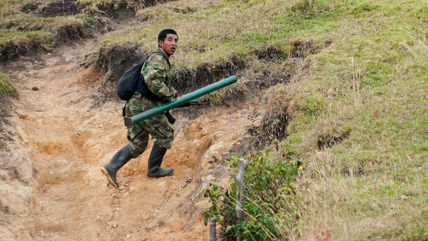 A member of the Revolutionary Armed Forces of Colombia, or FARC, runs to take position during a firefight with the Colombian army in the mountains of Cauca state on July 12. For now, fighting continues even as the two sides prepare for peace talks.
