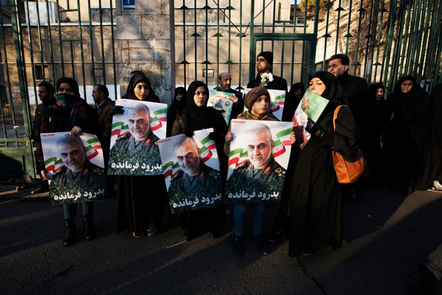 Crowds hold Soleimani's portrait while waiting for the traditional Muslim prayers for the dead to begin.