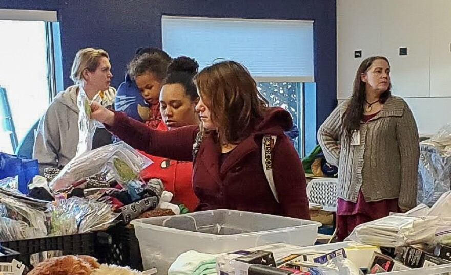 Photo of attendees of a homelessness wellness fair sort through bins of supplies.