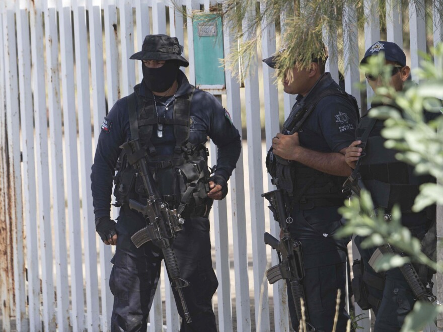 Mexican state police stand guard in May 2015 near a shootout between authorities and suspected criminals in Michoacan. Mexico's National Human Rights Commission said Thursday that 22 people were arbitrarily killed by federal police during that raid.