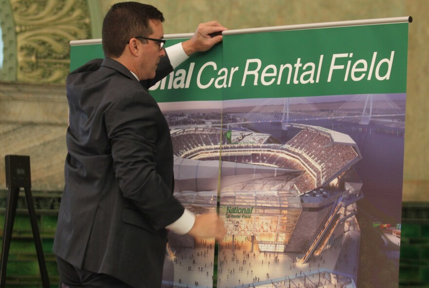 A member of the St. Louis stadium task force places signage in the room before the announcement that National Car Rental has agreed to pay $158 million over 20 years for naming rights for the proposed NFL stadium in St. Louis on October 7, 2015.