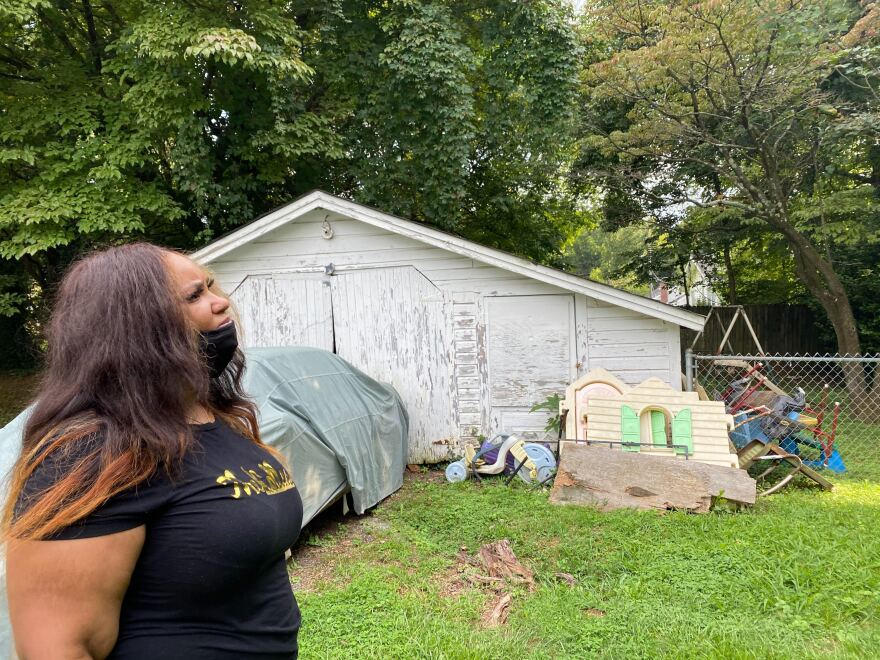 Alexus Johnson looks at the backyard of her great-grandmother's home in Washinton Heights, where many of the trees are 80 years old.