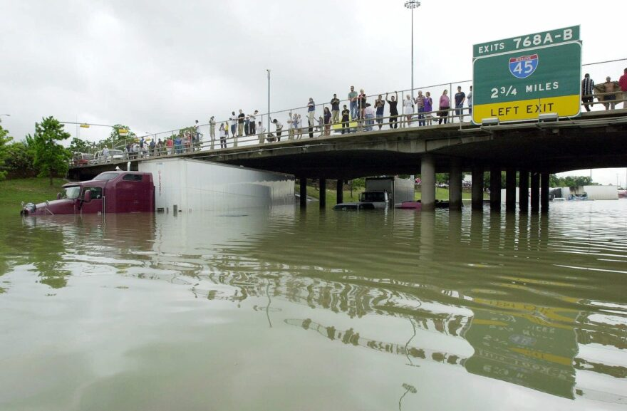Onlookers stand on an overpass where flood waters have covered Interstate 10 in Houston, Saturday, June 9, 2001. (AP Photo/Eric Gay)