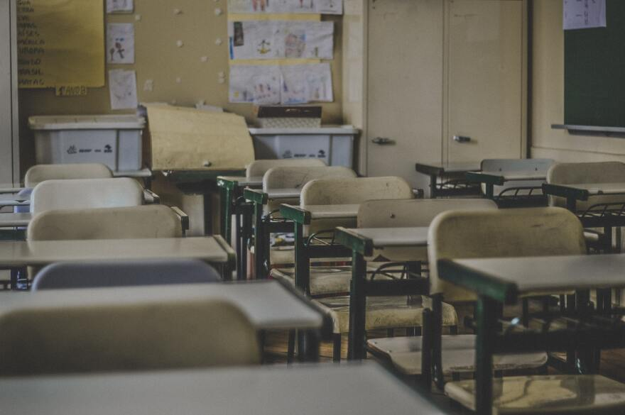 Empty desks sit in rows and columns in an empty classroom