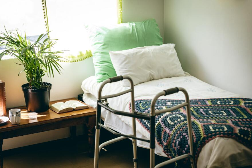 A walker rests beside a small nursing home bed.