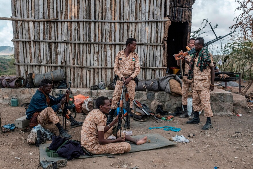 In November, Ethiopian government forces began fighting a powerful regional government in the country's northern Tigray region, displacing thousands. Members of the Afar Special Forces prepare their weapons on the outskirts of the village of Bisober in the Tigray region on Dec. 9. Several houses in the village were damaged during fighting between Tigrayan forces and the Ethiopian military.