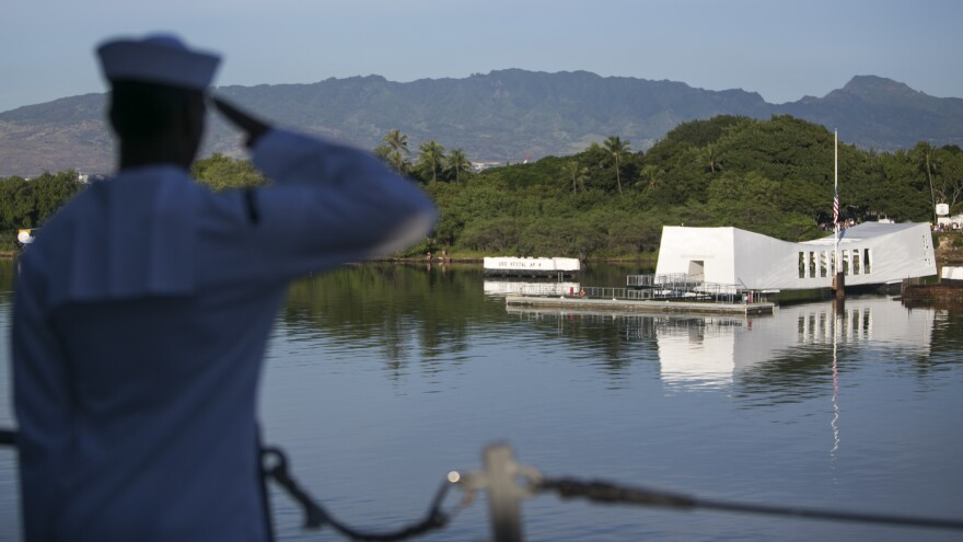 A Navy sailor salutes the memorial to the USS Arizona on Dec. 7, the 75th anniversary of the Japanese attack on Pearl Harbor. The Arizona was hit in the air raid.