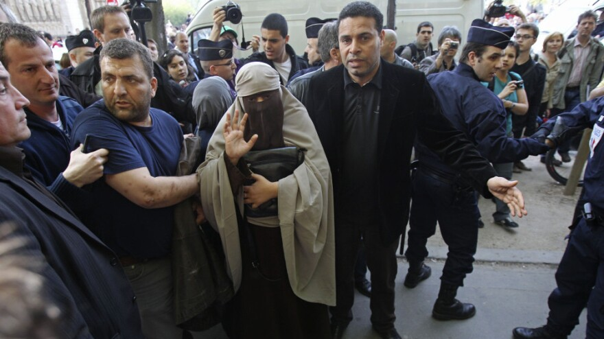 An unidentified veiled woman, flanked by friends, was taken away by police officers in Paris earlier today (April  11, 2011). France's new ban on Islamic face veils was met with a burst of defiance, as several women appeared veiled in front of Paris' Notre Dame Cathedral.