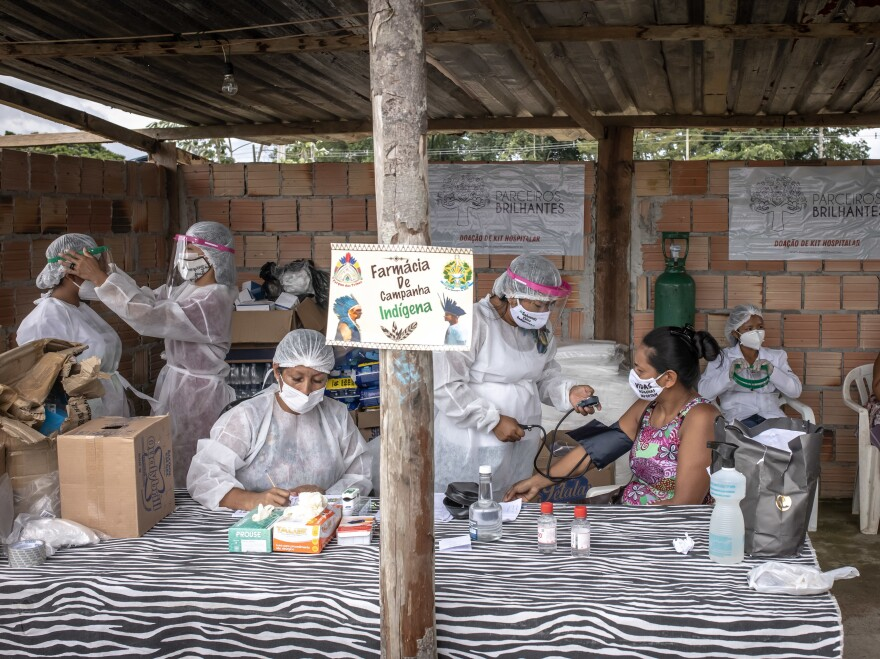 Indigenous healthcare workers wearing PPE treat patients at the Indian campaign hospital set up in the Parque das Tribos neighborhood of Manaus, Brazil, on Tuesday, Jan. 19, 2021. Severe oxygen shortages at hospitals in Brazil's Amazon prompted local authorities to impose a curfew and airlift patients to other states to deal with the onslaught of a second coronavirus wave.