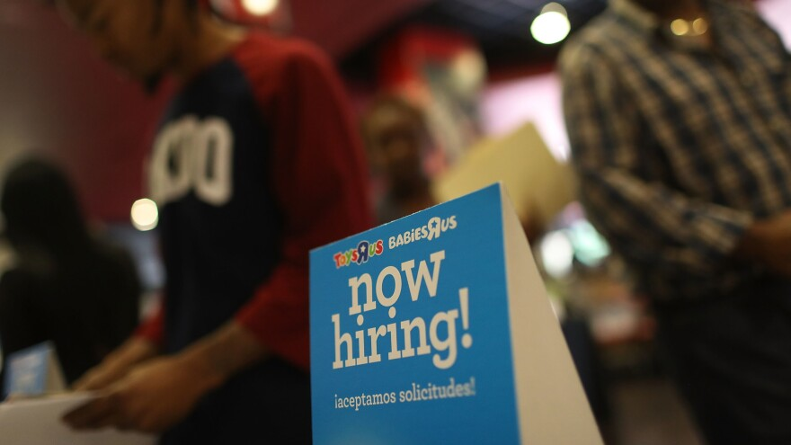 """A """"now hiring"""" sign is seen at the Toys R Us booth during the JobNewsUSA job fair at the BB&T Center in Sunrise, Fla., on Nov. 15."""