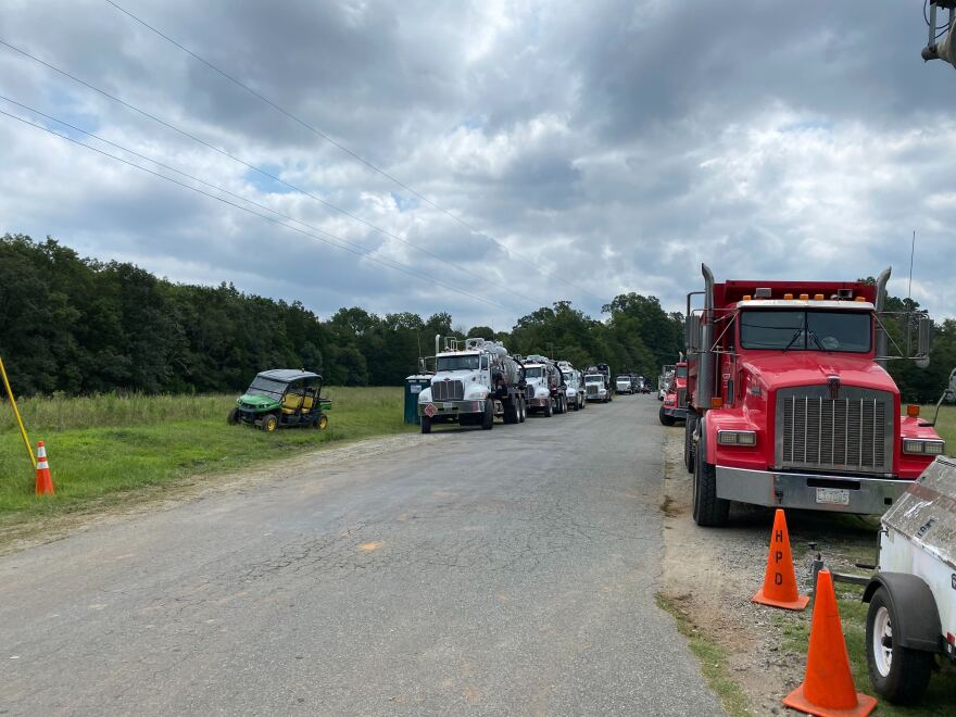 Dozens of heavy duty and pickup trucks line the sides of an off-road near Huntersville-Concord Road on Thursday August 20th. Colonial Pipeline said it had completed a repair of the leak by that evening.
