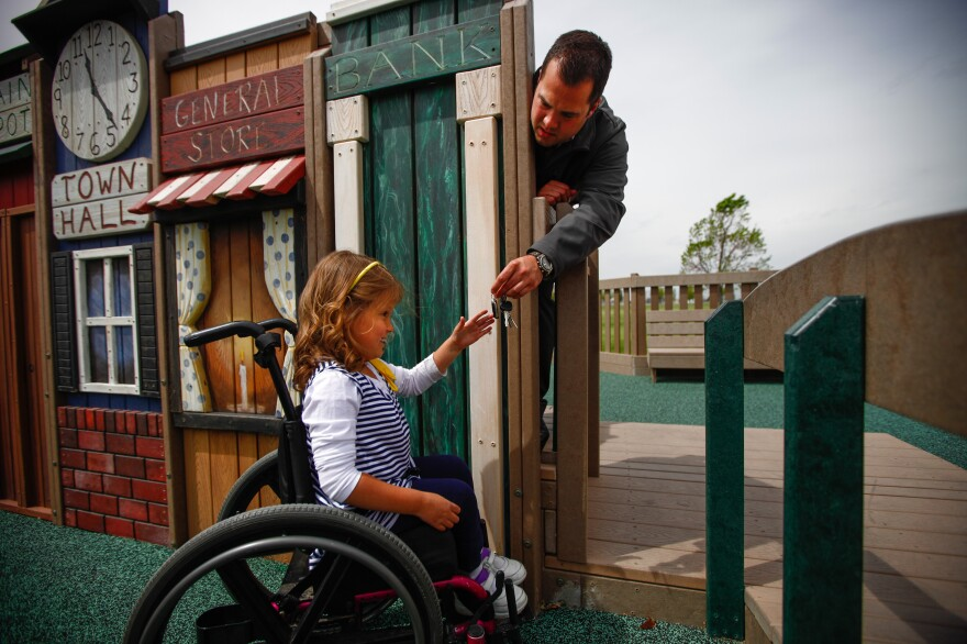 Brooklyn Fisher, who has spina bifida, plays with her father, Jonny Fisher, at the playground.