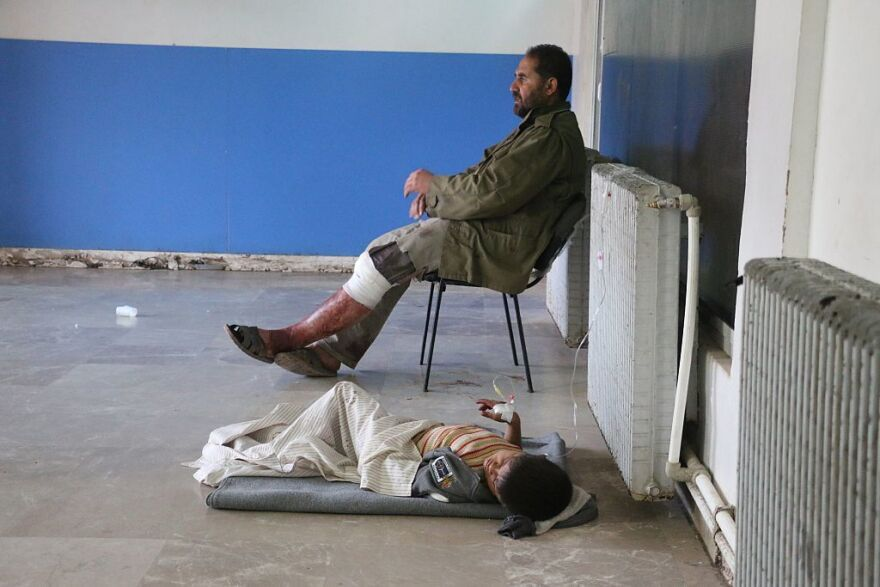 An injured man sits on a chair and a child lies on the floor as they receive medical treatment at a field hospital after an airstrike hit a refugee camp in Syria's Idlib province.